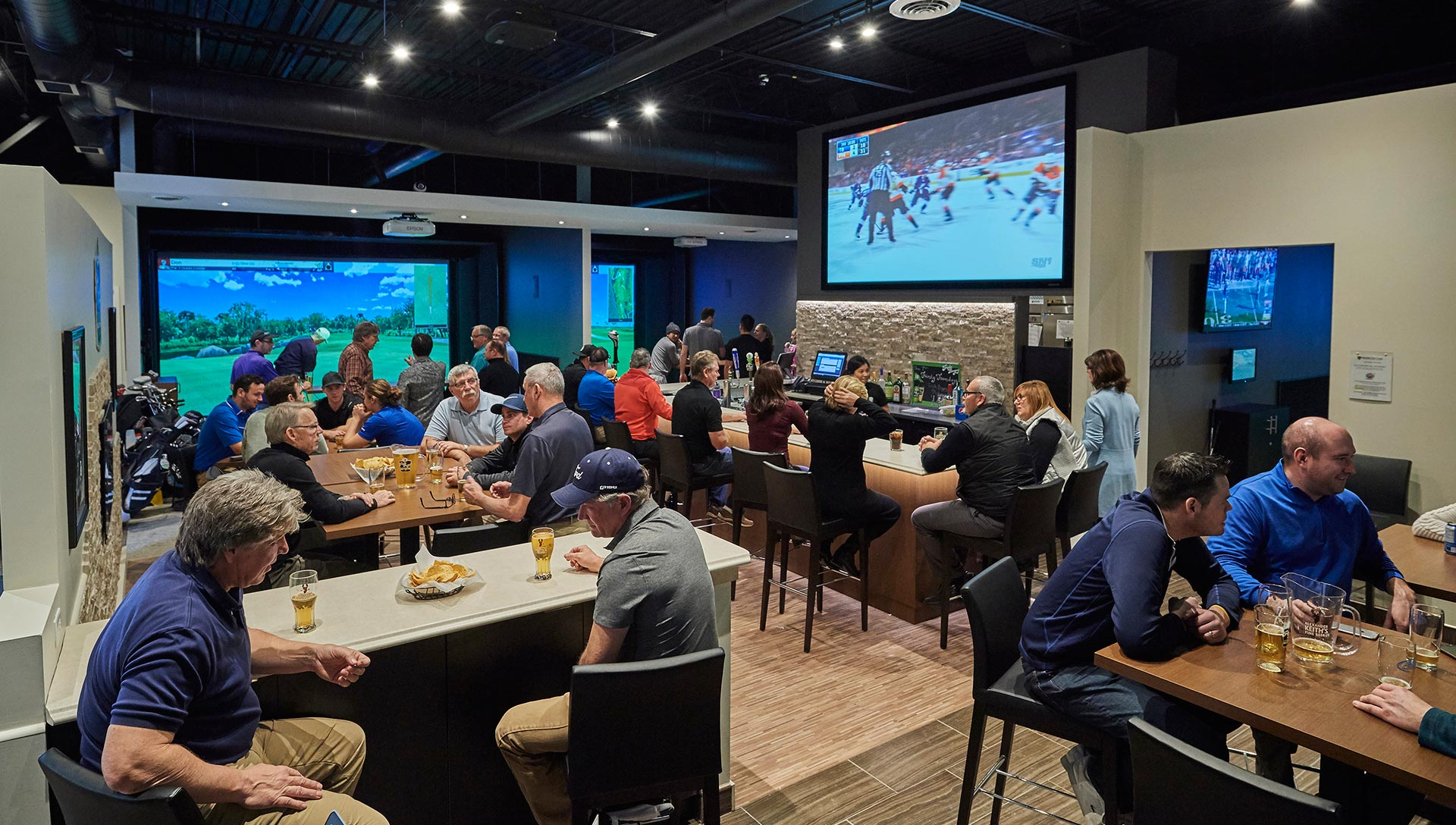 Indoor Golf Club and Sports Bar showing big screen TV and golf simulators.