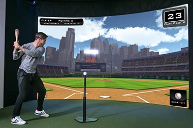Player hitting baseball at screen of sport simulator